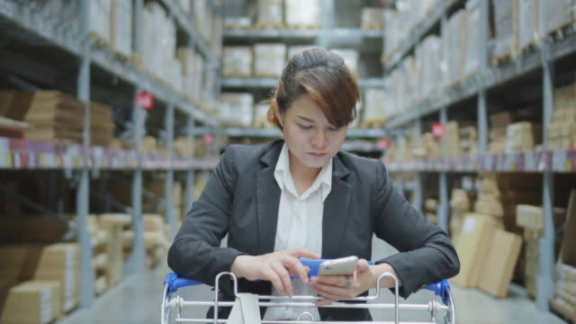 アジアの女性のモダンな倉庫、スローモーションでスマート フォンを使用して