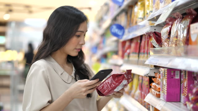 asian woman using smartphone in supermarket,slow motion - merchandise stock videos & royalty-free footage
