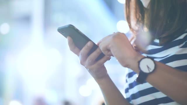 vídeos de stock, filmes e b-roll de mulher asiática usando smartphone na rua à noite - mensagem