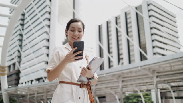 asian woman using smartphone looking at screen while walking outdoors in city - choosing stock videos & royalty-free footage