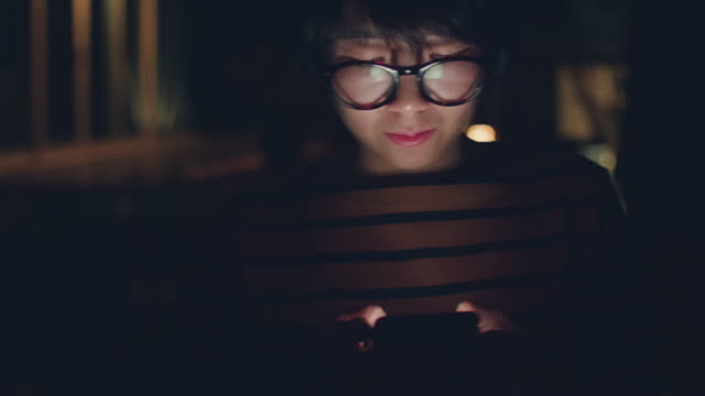 Asian woman using smartphone, night.