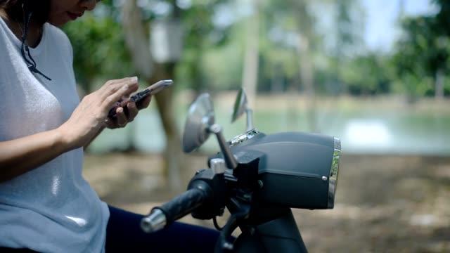 asiatische frau mit smartphone auf roller in der nähe des sees - motorroller stock-videos und b-roll-filmmaterial