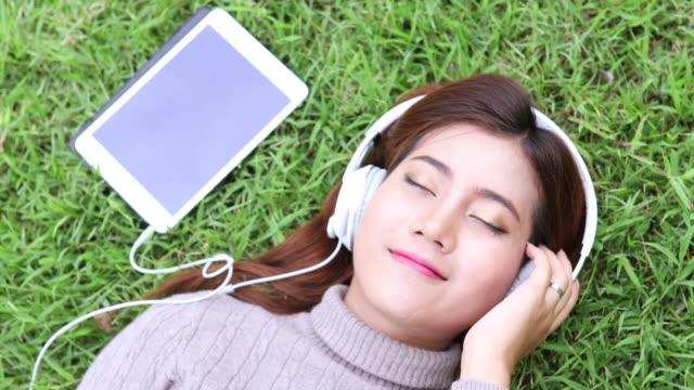stockvideo's en b-roll-footage met aziatische vrouw met behulp van tablet pc- en hoofdtelefoon in park voor ontspannen - zonnejurk
