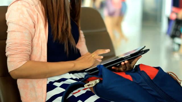 Asian woman using tablet at airport