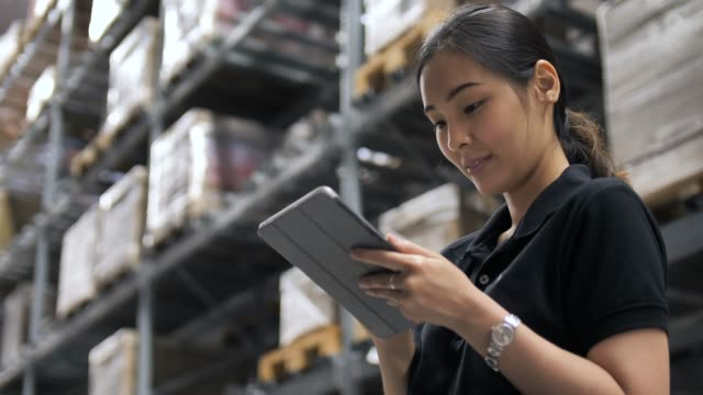 Asian Woman using Tablet Computer and Counts Merchandise in Warehouse