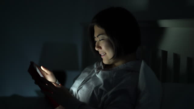 Asian woman using tablet in bed. M.S. RL Pan