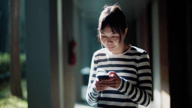 asiatische frau mit touchscreen-technologie auf dem smartphone - connection in process stock-videos und b-roll-filmmaterial