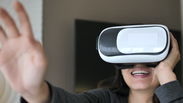 asian woman using vr glasses - realtà virtuale video stock e b–roll