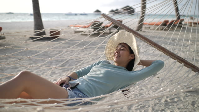 slow motion asian woman vacation in hammock at beach - napping stock videos & royalty-free footage
