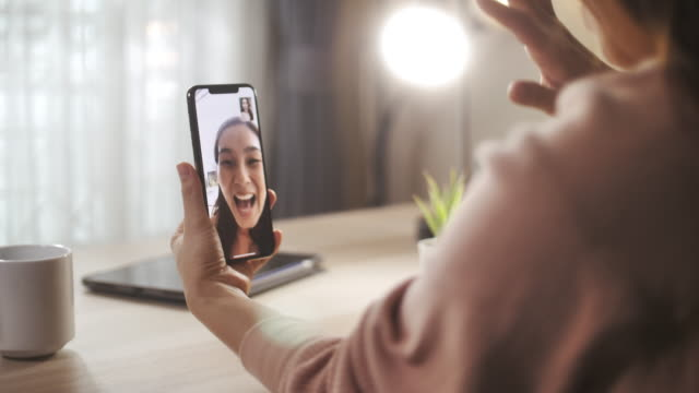 vídeos de stock, filmes e b-roll de asian woman video call on smart phone to her friend at home, social distancing - vídeo