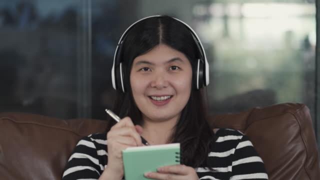 vídeos de stock e filmes b-roll de asian woman video conferencing and writing notes, working from home - aula de formação