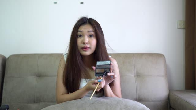 vídeos de stock, filmes e b-roll de mulher asiática vlogging sobre falar cosméticos de maquiagem em casa estúdio. ao vivo, gravando, blogueiro, streaming - blogar