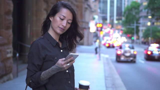 アジアの女性のタクシーを待っていると、スマート フォンを使用して - 組織点の映像素材/bロール