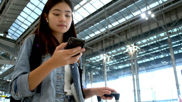 asiatische frau wartet auf reiseflug und mit dem telefon und sie ziehen sie den radkoffer in das passagiergebäude - flugpassagier stock-videos und b-roll-filmmaterial