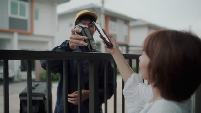 携帯電話で支払うオートバイに乗っている配達員から注文された食べ物を受け取るのを待っているアジアの女性 - order点の映像素材/bロール