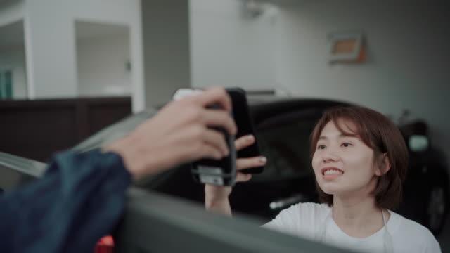 vídeos de stock, filmes e b-roll de mulher asiática esperando para receber comida encomendada de um entregador andando de moto pagando com celular - receber