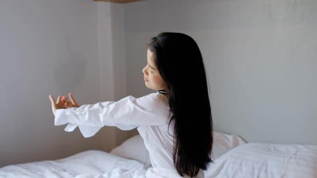 stockvideo's en b-roll-footage met aziatische vrouw wakker worden vernieuwd op ochtend in slaapkamer - strekken