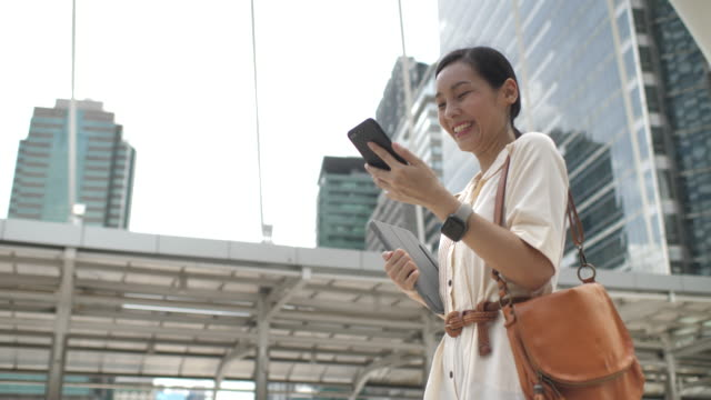 vídeos de stock e filmes b-roll de asian woman walking and using her smart phone in city - a caminho