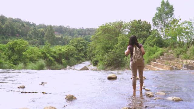 vidéos et rushes de femme asiatique marchant prudemment au bord de l'eau flottante pour regarder la forêt naturelle en face du déversoir local dans la scène de l'agriculture non urbaine, chaîne de montagnes, le nord de la thaïlande avec se sentir excité, émotion po - non urban scene