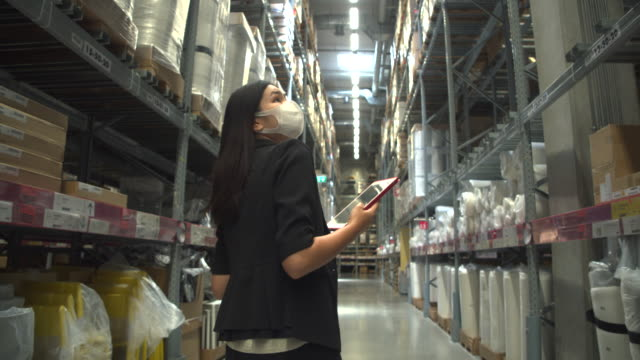 asian woman walking in the aisle of the warehouse and check the product using the internet via tablet. - touchpad stock videos & royalty-free footage