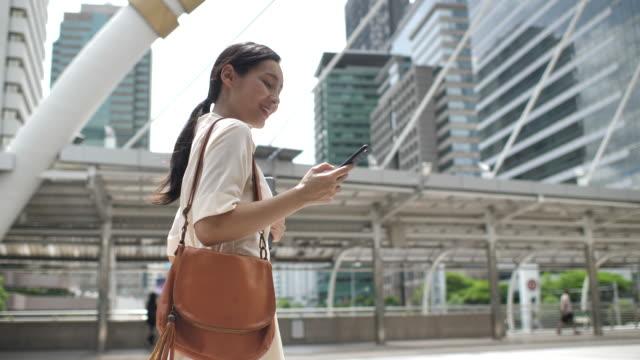 vídeos y material grabado en eventos de stock de mujer asiática caminando en la ciudad y usando el teléfono inteligente - vestimenta de negocios