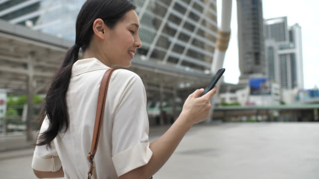 asian woman walking in the city and using smart phone - asian colleague stock videos & royalty-free footage
