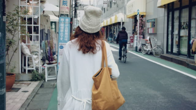 stockvideo's en b-roll-footage met aziatische vrouw lopen in de lokale stad in japan. - rear view