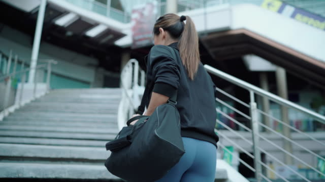 asian woman walking into fitness - building entrance stock videos & royalty-free footage