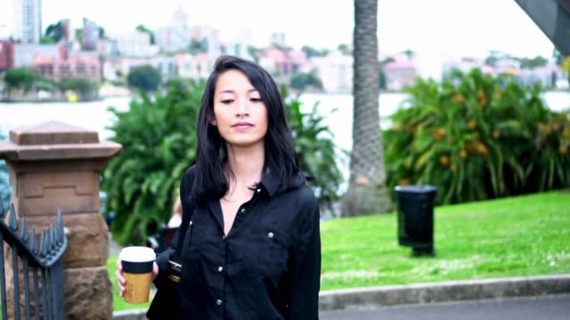 asian woman walking next to harbour bridge with reusable coffee cup, slo-mo - black hair stock videos & royalty-free footage
