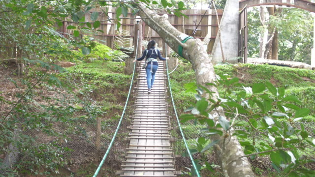 asian woman walking on a suspension bridge - footbridge stock videos & royalty-free footage
