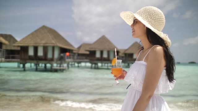 asiatische frau zu fuß am strand trinken orangensaft, gesundes essen und fitness lifestyle - eleganz stock-videos und b-roll-filmmaterial