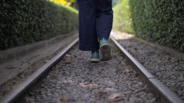 vidéos et rushes de femme asiatique marchant par le chemin de fer - voie ferrée