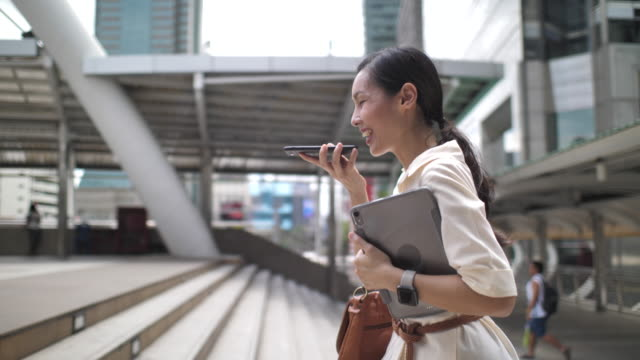 Asian Woman walking using voice recognition on phone in the City