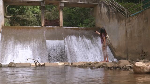 vidéos et rushes de femme asiatique marchant pieds nus devant le déversoir local dans la scène de l'agriculture non urbaine, chaîne de montagnes, prendre une photo de l'eau flottante comme une cascade, le nord de la thaïlande avec se sentir excité, émotion positive - non urban scene