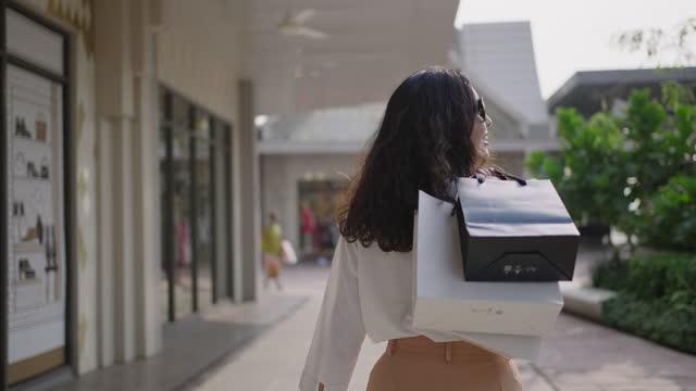 vidéos et rushes de femme asiatique marchant avec des sacs à provisions. fille de sourire flirtant sur l'appareil-photo - sac de shopping