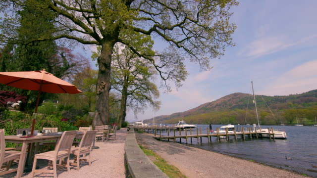 asian woman walks on lakeside pier lakeside, windermere, england - 突堤点の映像素材/bロール