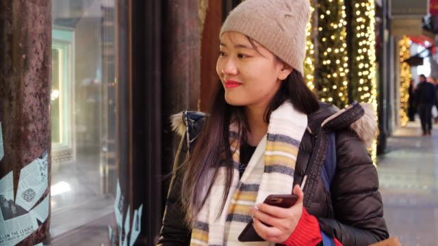 vídeos y material grabado en eventos de stock de asian woman walks up and takes photo of shop window - accesorio de cabeza