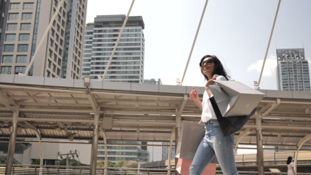 asian woman walks with shopping bags in the city - pavement stock videos & royalty-free footage
