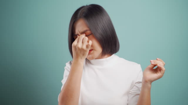 asian woman was sick with eyes pain and standing isolated over blue background. health care concepts. 4k video. - allergy stock videos & royalty-free footage