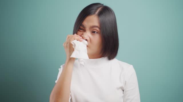 asiatische frau war krank mit fieber niesen und wischen snot durch gewebepapier stehen isoliert über blauem hintergrund. konzepte im gesundheitswesen. 4k video. - snuff stock-videos und b-roll-filmmaterial