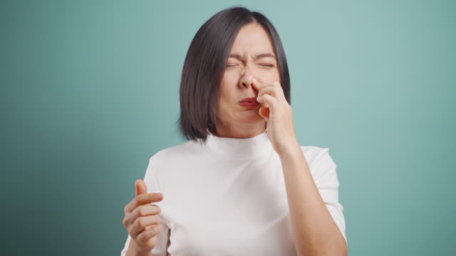 asian woman was sick with fever sneezing and wipe snot by tissue paper standing isolated over blue background. health care concepts. 4k video. - smelling stock videos & royalty-free footage