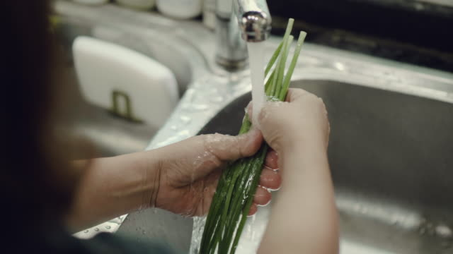 Asian woman washing and preparing vegetables