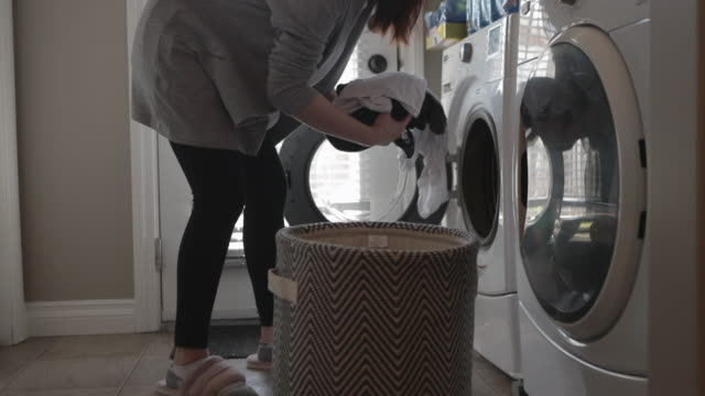 asian woman washing clothes in automatic laundry - mid adult stock videos & royalty-free footage