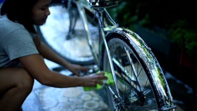 asian woman washing her beach cruiser at home. - belarus stock videos & royalty-free footage