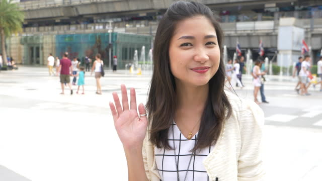 asian woman waving hand and smiling - waving hands stock videos & royalty-free footage