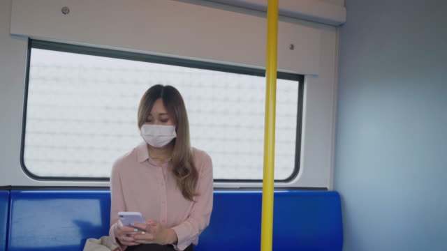 asian woman wear face mask using mobile phone sitting at airport - public transport stock videos & royalty-free footage