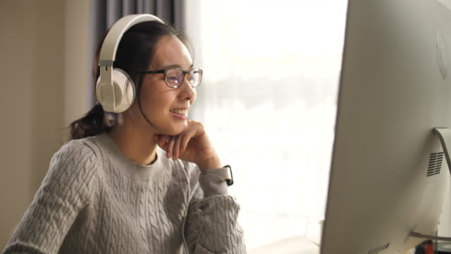asian woman wear headphone using computer at home - one young woman only stock videos & royalty-free footage