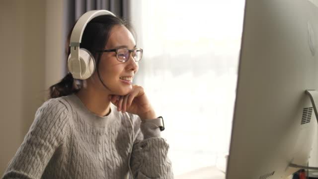 vídeos de stock, filmes e b-roll de auscultadores asiáticos do desgaste da mulher usando o computador em casa - só uma mulher jovem