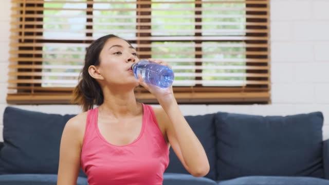アジアの女性は、リフレッシュ感と家庭でのリビングルームでヨガマット上の運動後の新鮮な水を飲むスポーツウェアを着用してください。健康ライフスタイル。ミディアムメックショット - ウォーターボトル点の映像素材/bロール