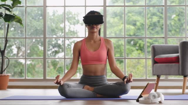 asiatische frau tragen virtual-reality-headset und sitzen auf matte mit lotus-pose heben arm nach oben und unten in namaste und layon knie. - gebetsposition stock-videos und b-roll-filmmaterial